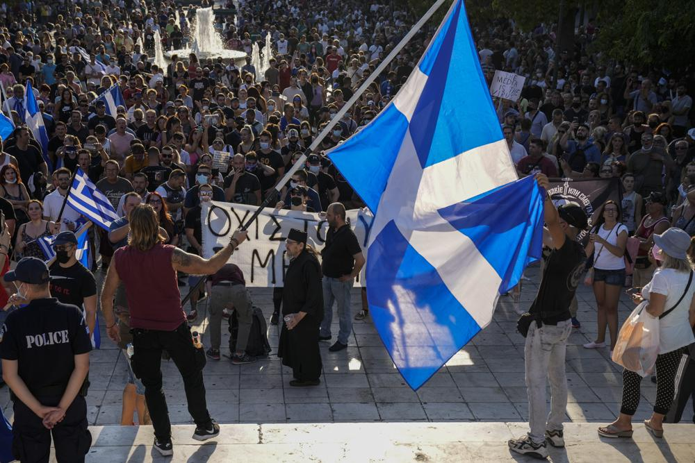 Anti-vaccine protester hold Greek flags during demonstration at Syntagma square, central Athens, on Wednesday, July 14, 2021.  Some thousands of anti-vaccine demonstrators gathered in Greece's two largest cities Wednesday over plans to make the vaccine available to children from age 15. Just over 50% of Greeks and country residents have received at least one dose of the COVID-19 vaccine.(AP Photo/Petros Giannakouris)