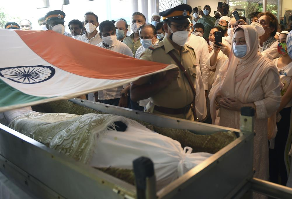"""A police officer places an Indian national flag over the coffin of Bollywood icon Dilip Kumar during his funeral in Mumbai, India, Wednesday, July 7, 2021. Dilip Kumar, hailed as the """"Tragedy King"""" and one of Hindi cinema's greatest actors, died Wednesday in a Mumbai hospital after a prolonged illness. He was 98."""