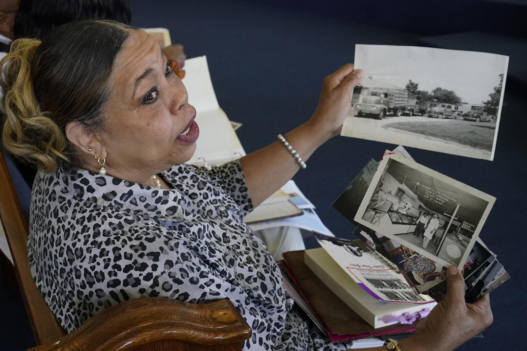 """Carolyn Roberts, daughter of Tulsa Race Massacre survivor Ernestine Alpha Gibbs, holds family photos of the Gibbs family business during an interview in Tulsa, Okla., on Sunday, April 11, 2021. Roberts said although her parents lived with the trauma of the massacre, it never hindered their work ethic: """"They survived the whole thing and bounced back."""" (AP Photo/Sue Ogrocki)"""