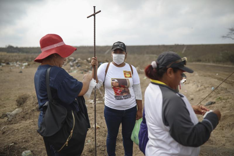 FILE - In this March 11, 2019 file photo, Lidia Lara Tobon, center, whose brother Angel Gabriel Tobon went missing, works with other relatives of the disappeared from the Solecito Collective, as they search for clandestine graves inside a municipal dump after an anonymous source sent the group a map  suggesting hundreds of bodies were buried in the area, in the port city of Veracruz, Mexico. The mainly female volunteer searchers who fan out across Mexico to dig for the bodies of their murdered relatives are themselves increasingly being killed, putting to the test the government's promise to help them in their quest for a final shred of justice: a chance to mourn.  (AP Photo/Felix Marquez, File)