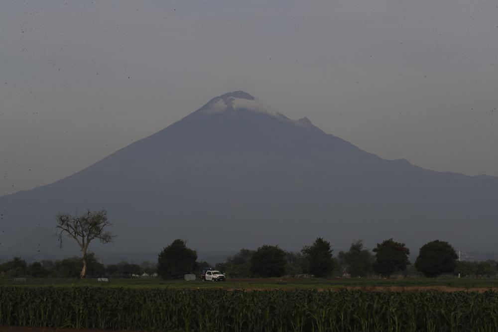 With the Popocatepetl volcano on the background, security personnel patrol the perimiter around a water filled sinkhole in Zacatapec, on the outskirts of Puebla, Mexico, Wednesday, June 9, 2021. The massive water-filled sinkhole continues swallowing farmers' fields in the central Mexican state of Puebla. (AP Photo/Fernando Llano)