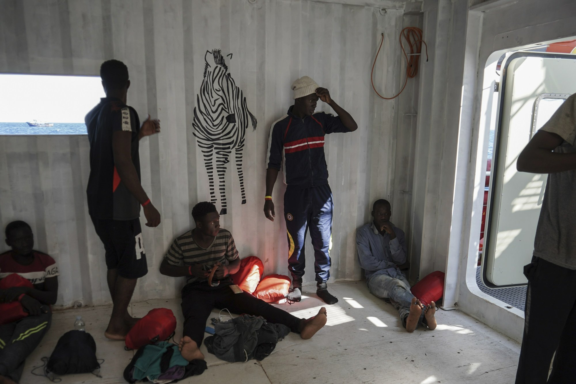 In this Sept. 8, 2019 photo, migrants rescued at sea by the NGOs SOS Mediterranée and Doctors Without Borders rest in the men's shelter aboard the Ocean Viking humanitarian ship as it sails in the Mediterranean Sea. The misery of migrants in Libya has spawned a thriving and lucrative business, in part funded by the EU and enabled by the United Nations, an Associated Press investigation has found. (AP Photo/Renata Brito)