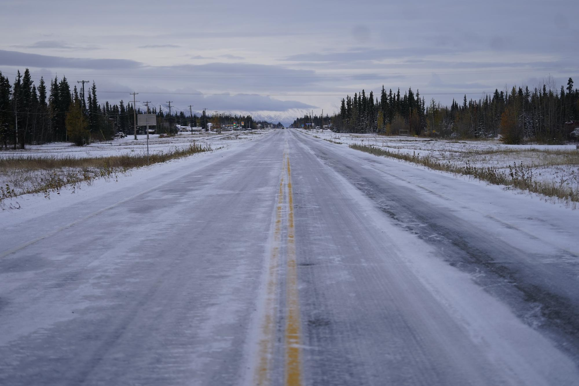 Ice and snow covers the Alaska Highway Wednesday, Sept. 22, 2021, in Tok, Alaska. The state is experiencing one of the sharpest rises in COVID-19 cases in the country, coupled with a limited statewide healthcare system that is almost entirely reliant on Anchorage hospitals. (AP Photo/Rick Bowmer)