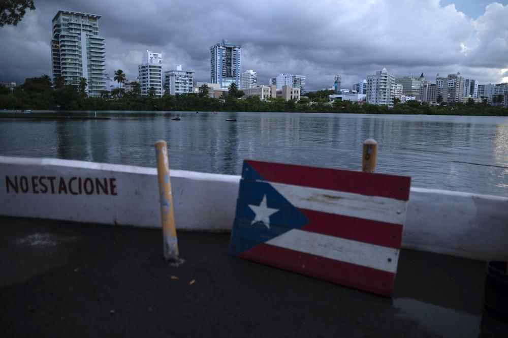 """FILE - In this Sept. 30, 2021 file photo, a wooden Puerto Rican flag is displayed on the dock of the Condado lagoon in San Juan, Puerto Rico. The number of people in Puerto Rico who identified as """"white"""" in the 2020 Census plummeted almost 80%, sparking a conversation about identity on an island breaking away from a past where race was not tracked and seldom debated in public. (AP Photo/Carlos Giusti, File)"""