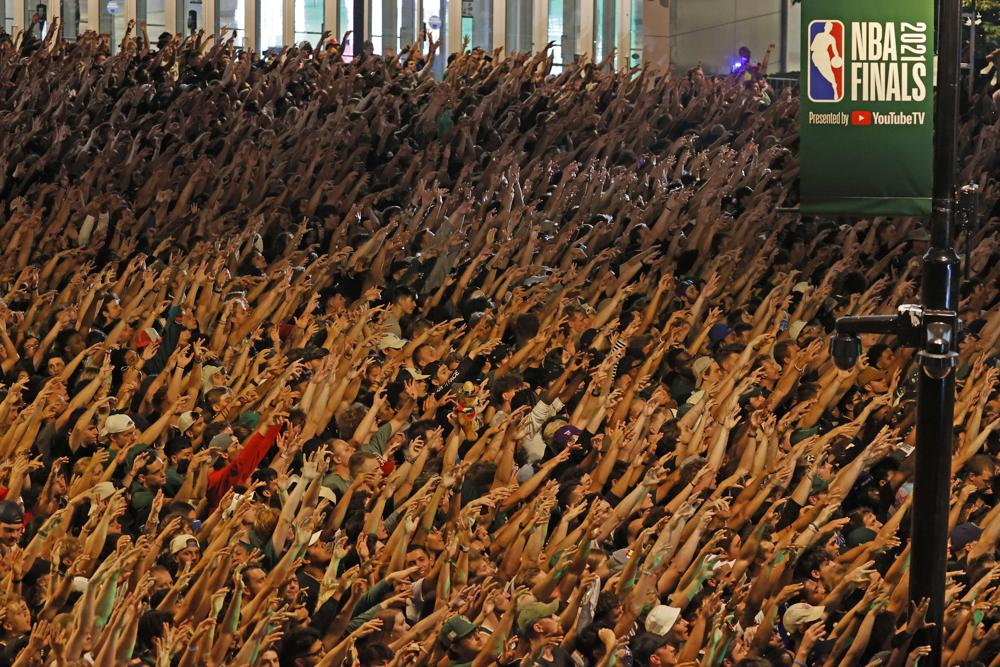 Fans raise their arms in union as they watch Game 6 of the NBA basketball finals game between the Milwaukee Bucks and Phoenix Suns Tuesday, July 20, 2021, in Milwaukee. (AP Photo/Jeffrey Phelps)