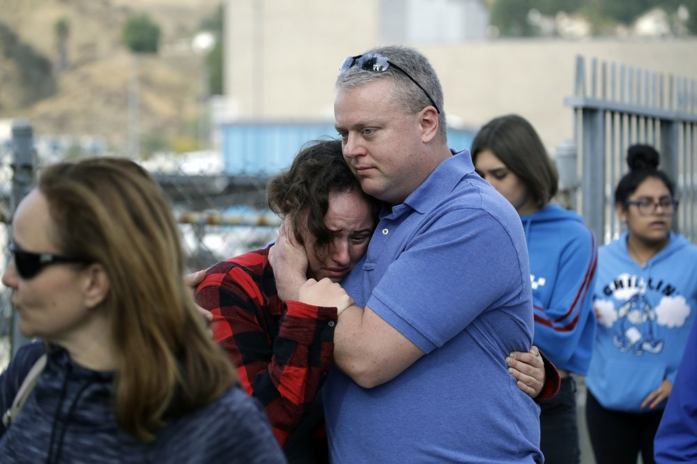 Students are escorted out of Saugus High School as some parents join them after reports of a shooting on Thursday, Nov. 14, 2019, in Santa Clarita, Calif. (AP Photo/Marcio Jose Sanchez)