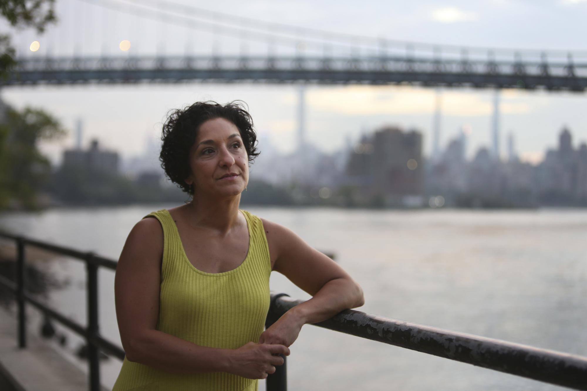 """Anthoula Katsimatides looks out over the East River from Astoria Park on Monday, Aug. 30, 2021, in the Queens borough of New York. Her brother John Katsimatides, who worked on the 104th floor of the World Trade Center's north tower, was killed in the Sept. 11, 2001 attacks. """"When we discovered ... that St. Nicholas was also lost, we thought that there was some kind of a message there, that the victims did not die alone,"""" Anthoula  said. """"I remember my mom saying that ... John and the other victims were being cradled by St. Nicholas."""" (AP Photo/Jessie Wardarski)"""