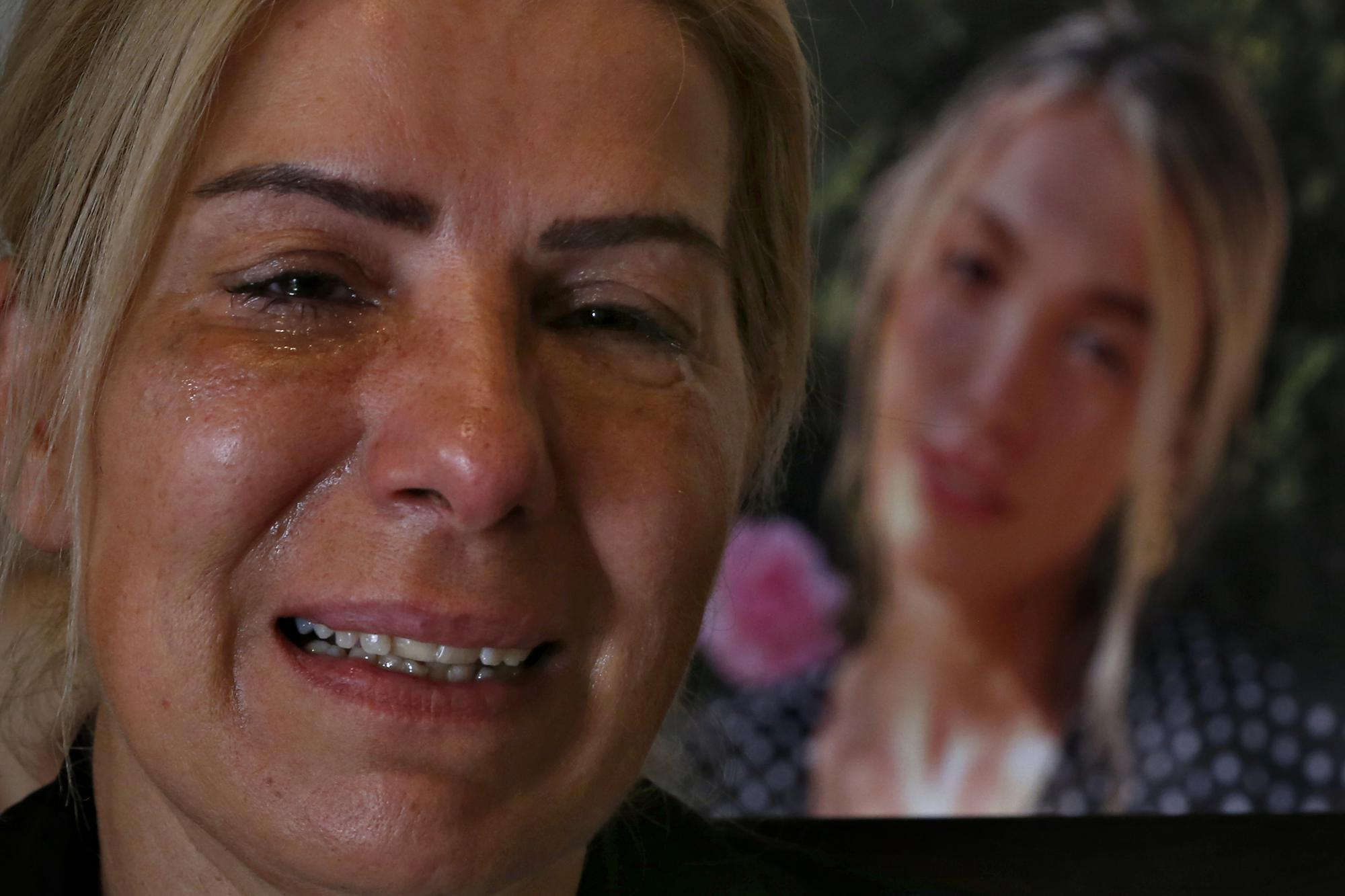 Chouchan Yeghiyan weeps in front of a picture of her daughter, Jessica Bezdjian, who was killed in last year's massive blast at Beirut's seaport, during an interview with The Associated Press at her home in Antelias, Lebanon, Monday, July 12, 2021. Bezidjian was one of four female nurses who lost their lives at the Saint George Hospital University Medical Center that day, including her close friend Jessica Kahwaji who was instantly killed. (AP Photo/Bilal Hussein)