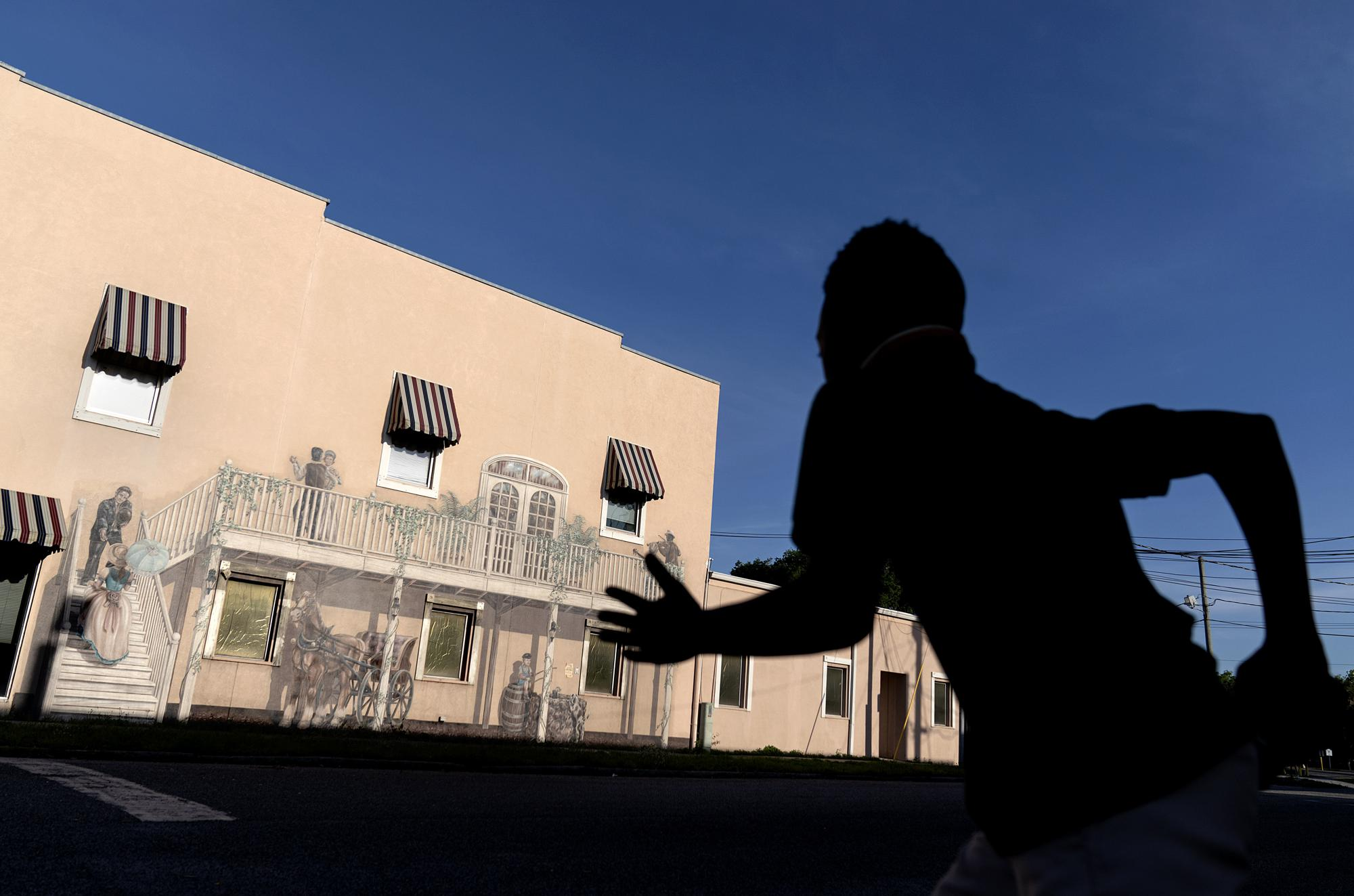 """A mural titled """"Bygone Days"""" decorates a downtown building as a child rushes to cross a street in Palatka, Fla., Tuesday, April 13, 2021. Jim Crow Florida was one of the most dangerous places in the South to be Black. In that era, a Black man in Florida was more at risk of being lynched - an execution without trial, often by gun or hanging - than in any other state, according to a University of Georgia study of lynching records. (AP Photo/David Goldman)"""