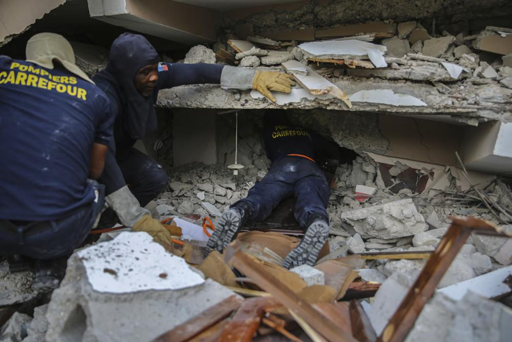 Firefighters search for survivors inside a collapsed building, after Saturday´s 7.2 magnitude earthquake in Les Cayes, Haiti, Sunday, Aug.  15, 2021. (AP Photo/Joseph Odelyn)