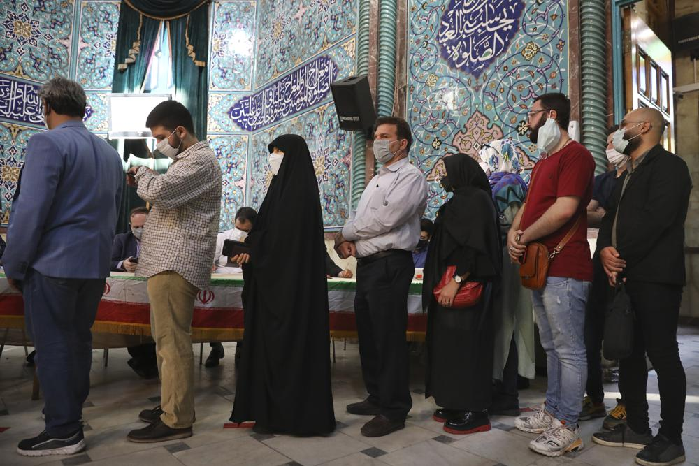 Voters queue at a polling station during the presidential elections in Tehran, Iran, Friday, June 18, 2021. Iranians vote Friday in a presidential election dominated by a hard-line protege of Supreme Leader Ayatollah Ali Khamenei after authorities disqualified nearly all of his strongest competition, leading to what appeared to be a low turnout fueled by apathy and calls for a boycott.  (AP Photo/Vahid Salemi)