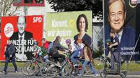 FILE - In this Thursday, Sept. 23, 2021 file photo, People walk and drive past election posters of the three candidates for German chancellor , from right, Armin Laschet, Christian Democratic Union (CDU), Annalena Baerbock, German Green party (Die Gruenen) and Olaf Scholz, Social Democratic Party (SPD), at a street in Gelsenkirchen, Germany. Germany's closely fought election on Sunday will set the direction of the European Union's most populous country after 16 years under Angela Merkel, whose party is scrambling to avoid defeat by its center-left rivals after a rollercoaster campaign. (AP Photo/Martin Meissner, File)