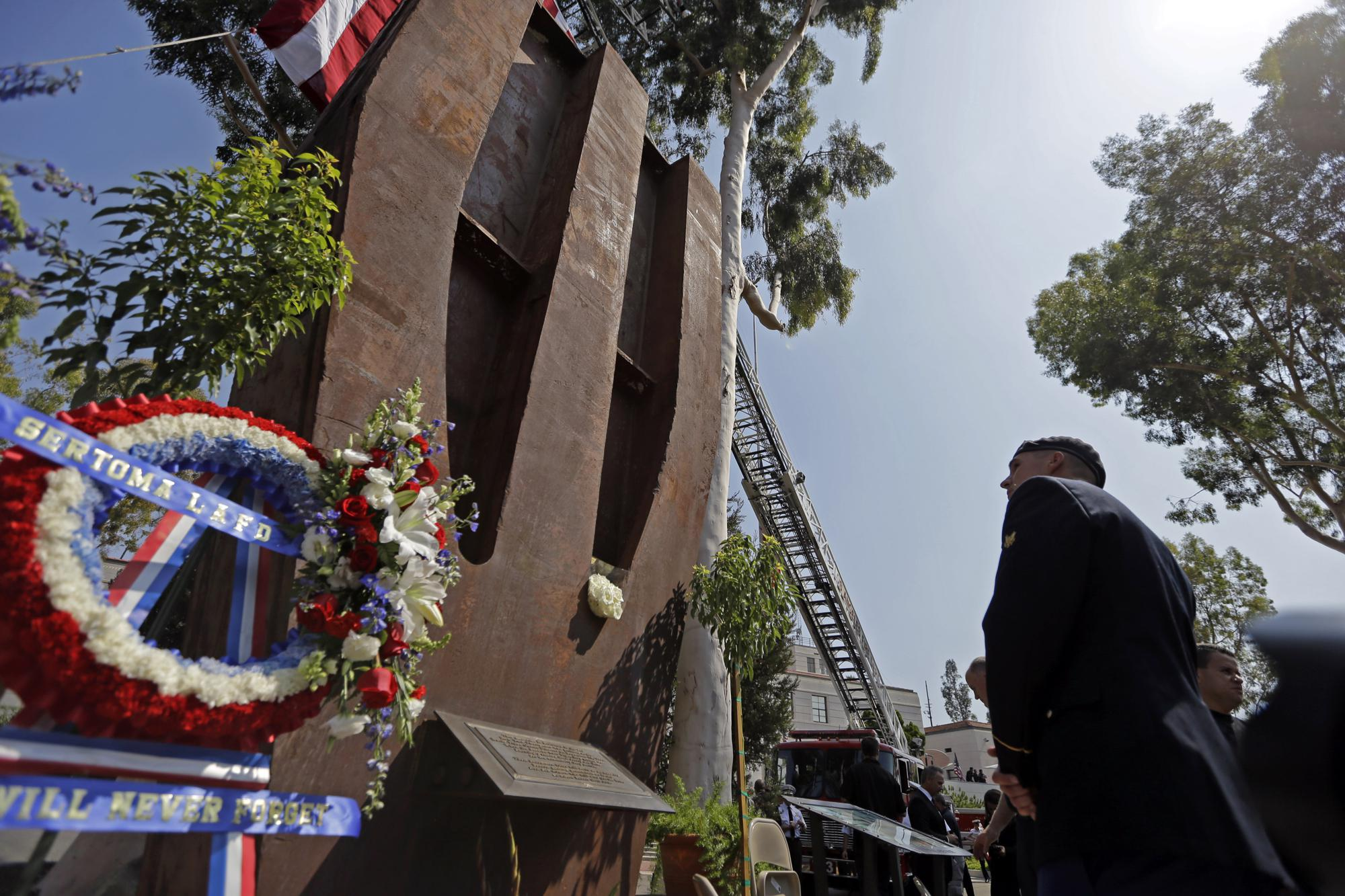 ADVANCE FOR PUBLICATION ON SUNDAY, SEPT. 5, AND THEREAFTER - FILE - In this Wednesday, Sept. 11, 2013 file photo, a U.S. army soldier pauses at a column from the South Tower of the World Trade Center at the Los Angeles Fire Department's Sept. 11 remembrance ceremony in Los Angeles. (AP Photo/Reed Saxon, File)