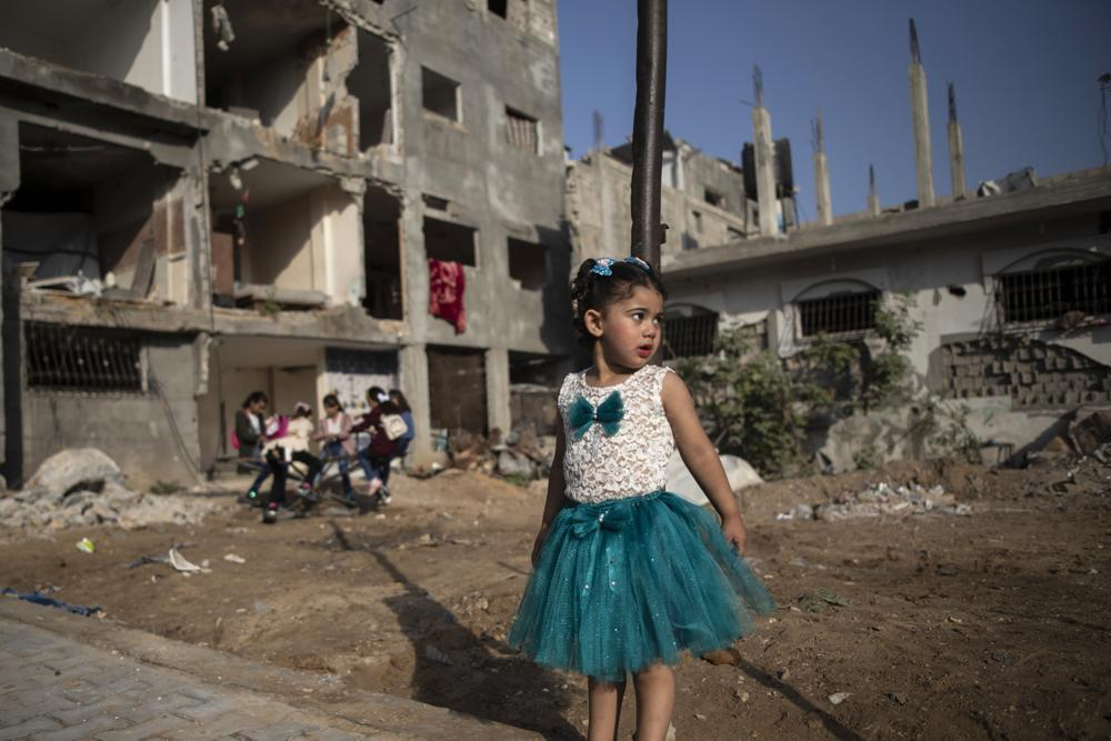 Dressed up to celebrate the first day of Eid al-Adha, Jana Zaanin, 3, stands near destroyed homes in town of Beit Hanoun, northern Gaza Strip, Tuesday, July 20, 2021. Eid al-Adha, or the festival of sacrifice, is celebrated by Muslims around the world to commemorate Prophet Ibrahim's test of faith. (AP Photo/Khalil Hamra)