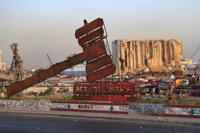 FILE - In this Aug. 4, 2021 file photo, a monument that represents justice stands in front of towering grain silos that were gutted in the massive August 2020 explosion at the port that killed more than 200 people and wounded over 6,000, in Beirut, Lebanon. For eight months Tarek Bitar, a relatively obscure judge has quietly investigated one of the world's worst non-nuclear explosions with only two assistants helping him -- and a lot of powerful detractors blocking him. For many Lebanese Bitar is their only hope for truth and accountability in a country that craves both. But for the country's entrenched political class, the 47-year-old Bitar has become a nightmare that needs to be dealt with. (AP Photo/Hussein Malla, File)