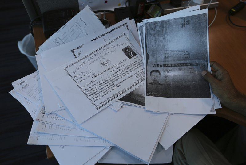 In this photo taken on May 27, 2019, a person shows photocopies of dozens of marriage contracts and other documents collected by a Pakistani security agency, in Islamabad, Pakistan. An elaborate trafficking scheme that lured poor Pakistani girls to China, some sold into prostitution, others locked away in remote rural China begging to return home, emerges amid arrests and testimony from frightened victims. (AP Photo/B.K. Bangash)
