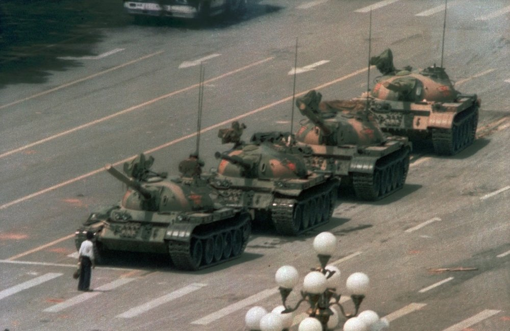 FILE - In this June 5, 1989 file photo, a Chinese man stands alone to block a line of tanks heading east on Beijing's Changan Blvd. in Tiananmen Square. The man, calling for an end to the recent violence and bloodshed against pro-democracy demonstrators, was pulled away by bystanders, and the tanks continued on their way. Over seven weeks in 1989, student-led pro-democracy protests centered on Beijing's Tiananmen Square became China's greatest political upheaval since the end of the Cultural Revolution more than a decade earlier.(AP Photo/Jeff Widener, File )