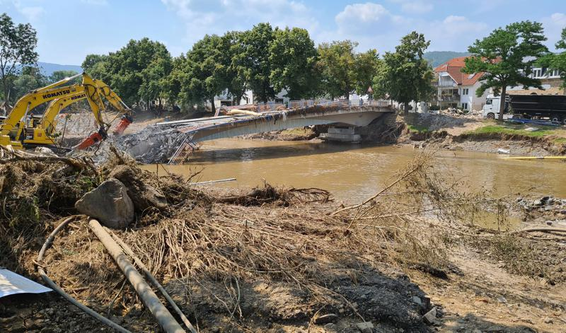 Workers use heavy machines to tear down a damaged bridge in the flood-hit town of Ahrweiler, Germany, on Friday, July 23, 2021. With the death toll and economic damage from last week's floods in Germany continuing to rise, questions have been raised about why systems designed to warn people of the impending disaster didn't work. (AP Photo/Frank Jordans)