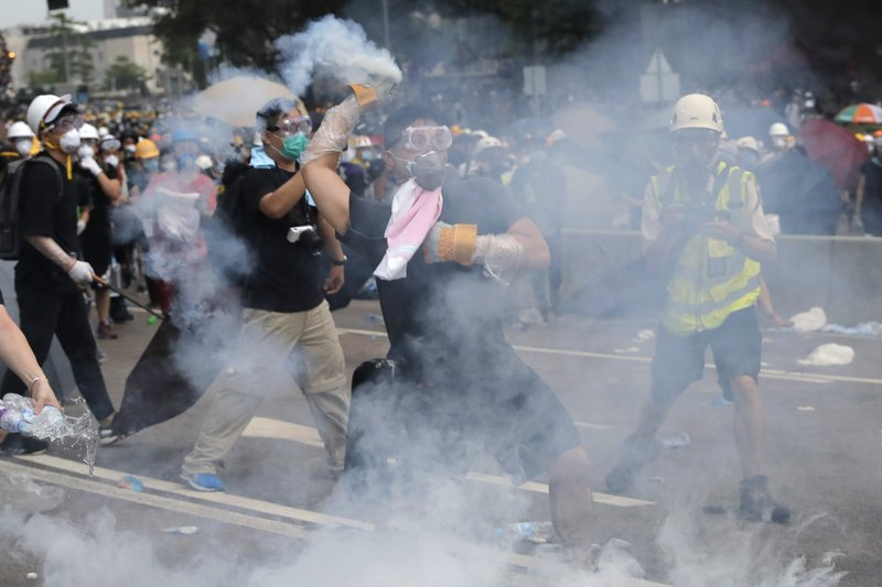 A demonstrator throws a canister of tear gas back towards the police outside the Legislative Council in Hong Kong, June 12, 2019. (AP Photo/Kin Cheung)