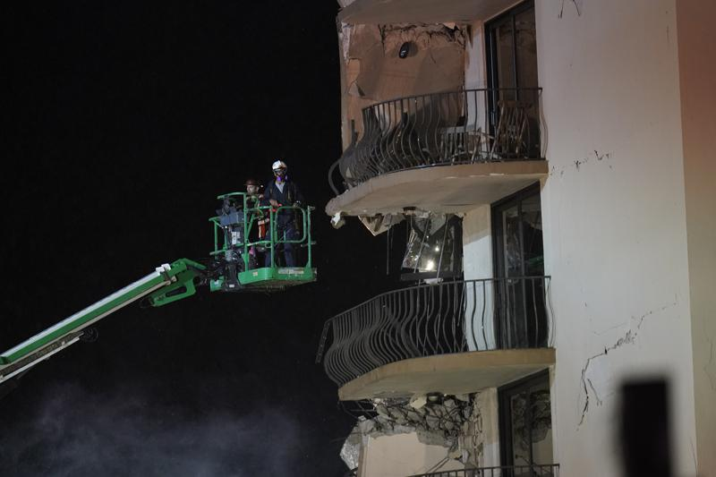 Workers use a lift to investigate balconies in the still-standing portion of the building, as rescue efforts continue where a wing of a 12-story beachfront condo building collapsed, late on Thursday, June 24, 2021, in the Surfside area of Miami.(AP Photo/Gerald Herbert)