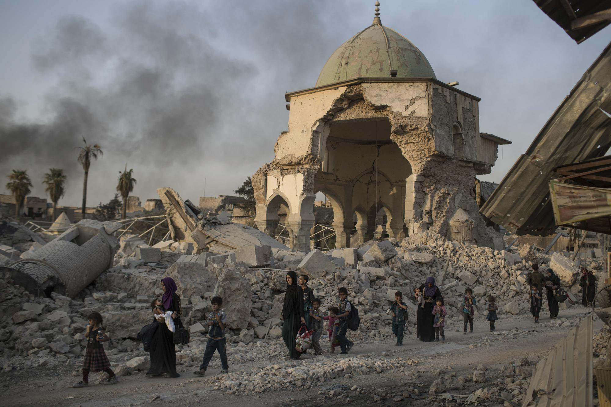 FILE - In this Tuesday, July 4, 2017 file photo, fleeing Iraqi civilians walk past the heavily damaged al-Nuri mosque as Iraqi forces continue their advance against Islamic State militants in the Old City of Mosul, Iraq. As Iraqi forces continued to advance on the last few hundred square kilometers of Mosul held by the Islamic State group, the country's Prime Minister said Tuesday the gains show Iraqis reject terrorism. (AP Photo/Felipe Dana, File)