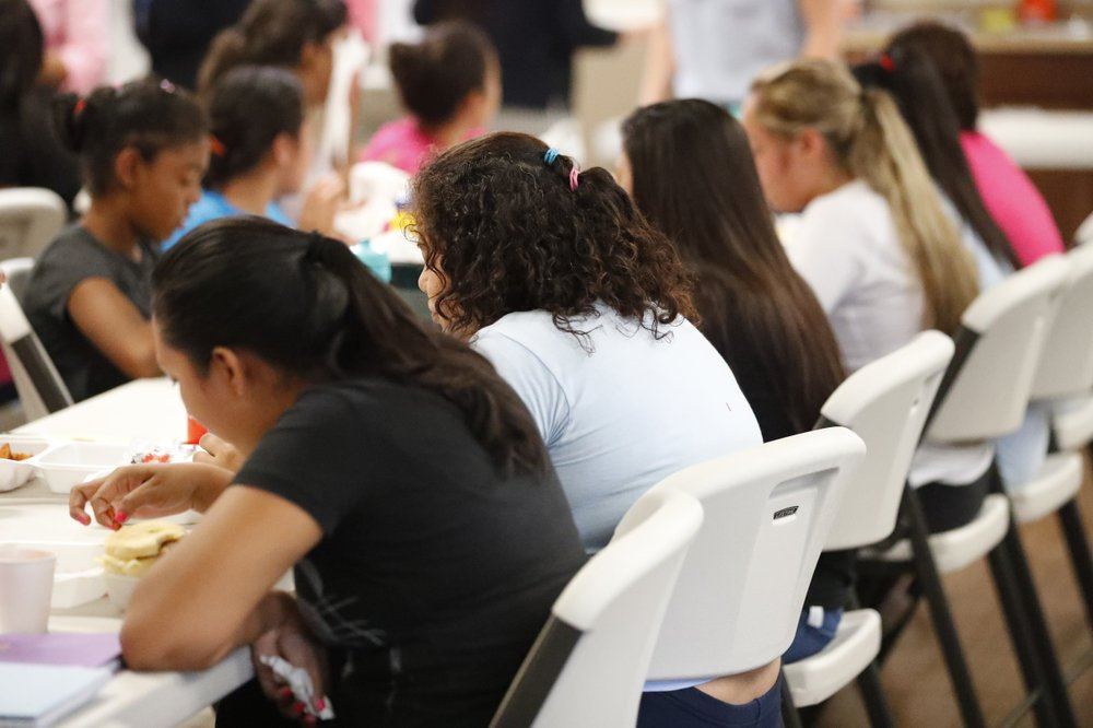 In this Sept. 24, 2019 photo, girls eat lunch at a shelter for migrant teenage girls, in Lake Worth, Fla. The nonprofit U.S. Committee for Refugees and Immigrants opened the federally funded Rinconcito del Sol shelter, aiming to make it a model of excellence in a system of 170 detention centers, residential shelters and foster programs which held nearly 70,000 migrant kids in the past year. (AP Photo/Wilfredo Lee)