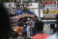 Commuters ride a Tap Tap bus in Port-au-Prince, Haiti, Wednesday, Oct. 20, 2021. (AP Photo/Matias Delacroix)