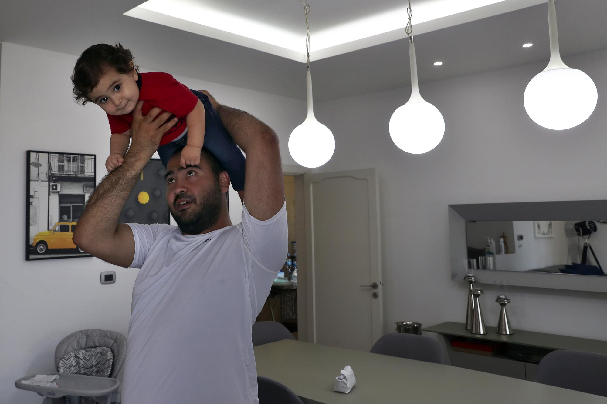 Edmond Khnaisser holds up his son, one-year-old Georges, at his house in the town of Jal el-Dib, north of Beirut, Lebanon, Tuesday, July 10, 2021. Khnaisser's wife, Emmanuelle, was about to give birth to her first son and was in the last stages of labor when the massive blast tore through the hospital, smashing windows, doors and machines in the operations room and riddling her lower body with tiny pieces of flying glass. (AP Photo/Bilal Hussein)