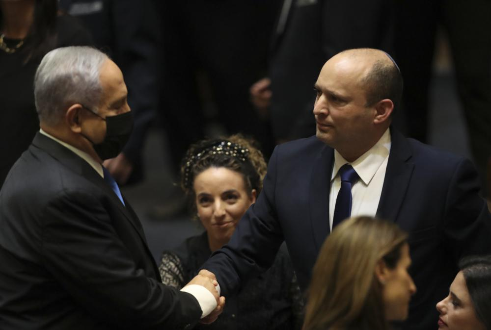 Israel's new prime minister Naftali Bennett shakes hands with outgoing prime minister Benjamin Netanyahu during a Knesset session in Jerusalem Sunday, June 13, 2021. Israel's parliament has voted in favor of a new coalition government, formally ending Netanyahu's historic 12-year rule. Naftali Bennett, a former ally of Netanyahu became the new prime minister (AP Photo/Ariel Schalit)