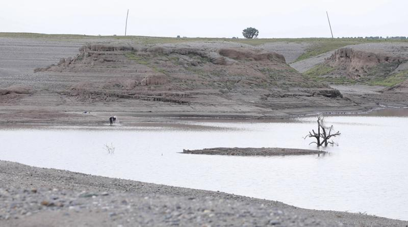 In this photo taken from a video shot on Wednesday, Aug. 4, 2021 in Wad el-Hilu, Sudan, a man washes in the Setit river, known in Ethiopia as Tekeze River. Locals and refugees have pulled dozens from bodies from the river separating Ethiopia's troubled Tigray region from Sudan in the past week, many with bullet wounds and their hands bound. Witnesses say that they are ethnic killings committed by Ethiopian government forces of Tigrayans, and that the bodies are being dumped to conceal the evidence. There was no immediate comment from the Ethiopian government but it has denied ethnic killings in the past.  (AP Photo/Mohaned Awad)