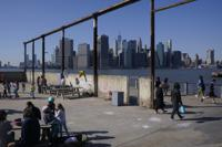 FILE - In this March 21, 2021, file photo people enjoy the sunny weather and a view of the Manhattan skyline from the Brooklyn waterfront in New York. The surge in the nation's urban population could give these urban centers greater influence in reshaping the balance of power in Washington as congressional redistricting gets under way. New York in particular is giving Democrats hope. The most populous city in the United States added some 629,000 new residents. (AP Photo/Seth Wenig, File)