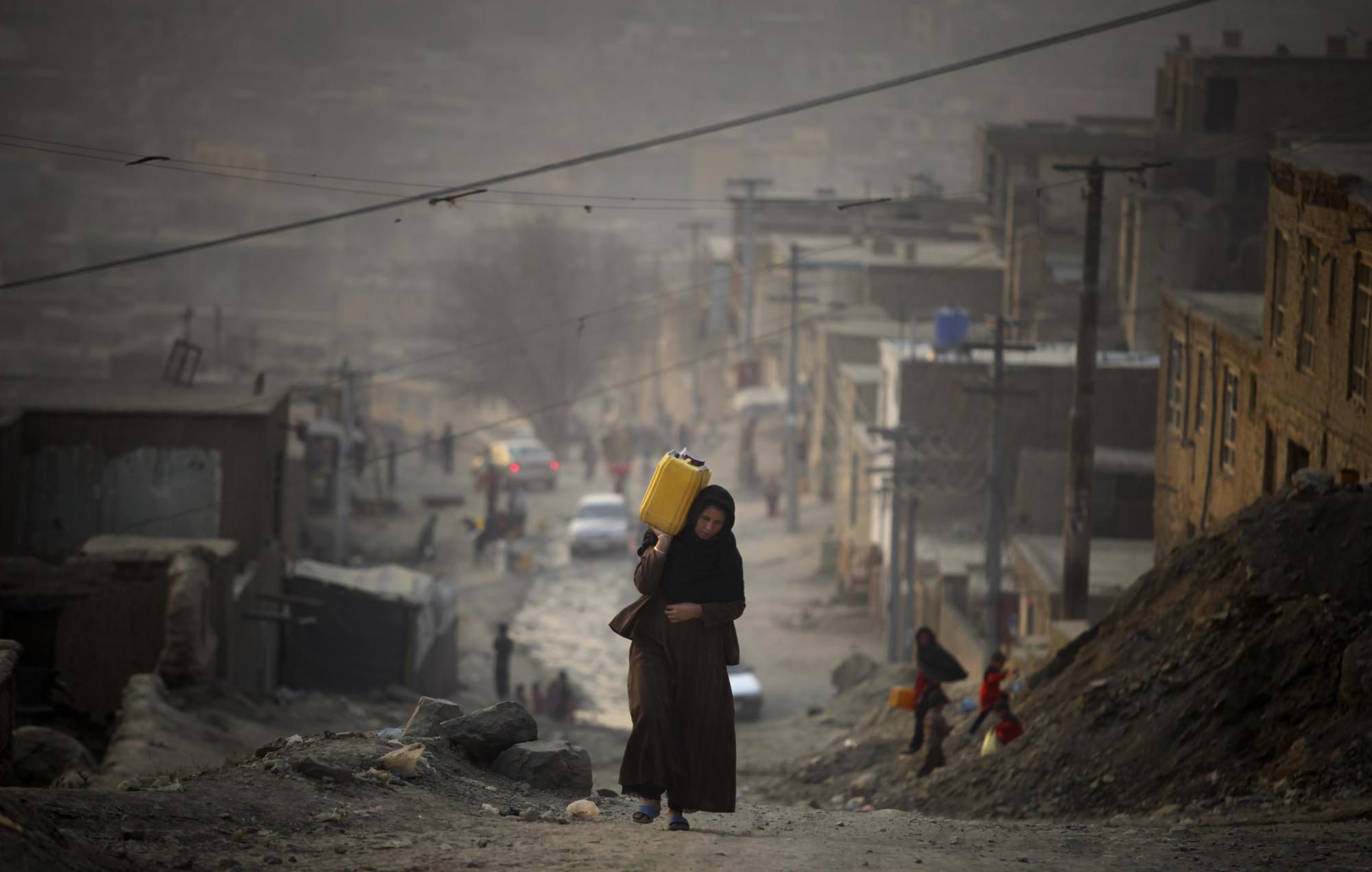 FILE - In this Dec. 27, 2010 file photo, a woman carries water in a plastic container as she ascends a slope on the way towards her home in Kabul, Afghanistan. (AP Photo/Altaf Qadri, File)