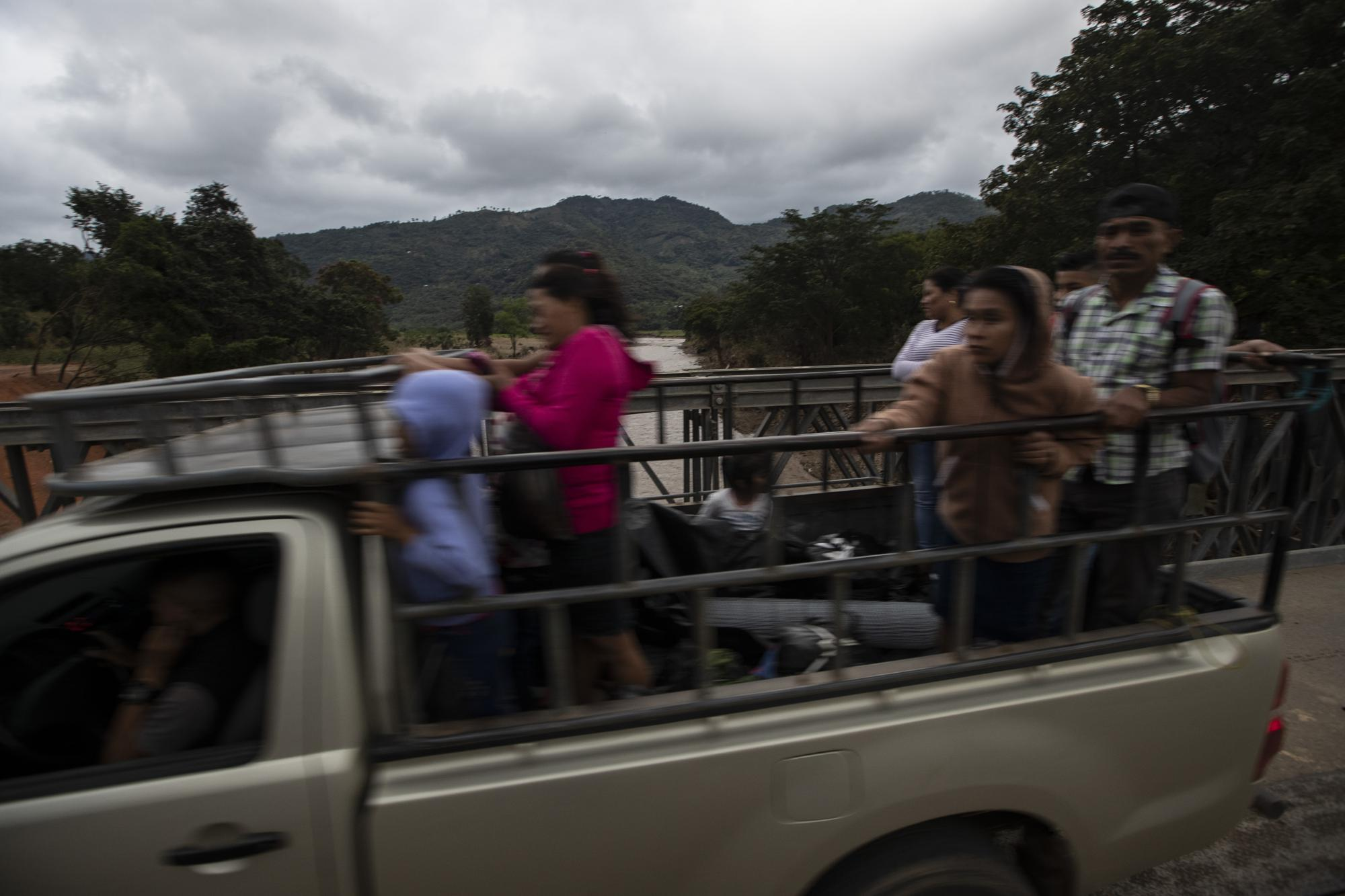 People ride on a temporary replacement bridge across the Jupilingo River to Tizamarte, Guatemala, Tuesday, Dec. 8, 2020, after the river overflowed during Hurricane Eta. President Joe Biden put Vice President Kamala Harris in charge of finding ways to address the root causes of migration, including poverty, corruption, violence and climate change. (AP Photo/Moises Castillo)