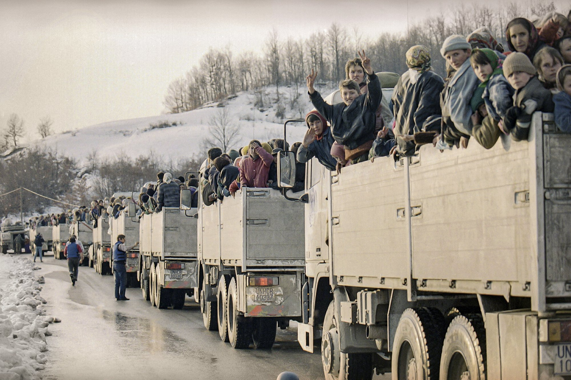 FILE- In this Monday, March 29, 1993 file picture, more than 2,000 evacuees from the besieged Muslim enclave of Srebrenica, packed on U.N. trucks en route to Tuzla, halt in Tojsici. The evacuation was possible due to a rare ceasefire in the area.  Survivors of the genocide in the eastern Bosnian town of Srebrenica, mainly women, will on Saturday July 11, 2020, commemorate the 25th anniversary of the slaughter of their fathers and brothers, husbands and sons.  At least 8,000 mostly Muslim men and boys were chased through woods in and around Srebrenica by Serb troops in what is considered the worst carnage of civilians in Europe since World War II. The slaughter was also the only atrocity of the brutal war that has been confirmed an act of genocide. (AP Photo/Michel Euler, File)
