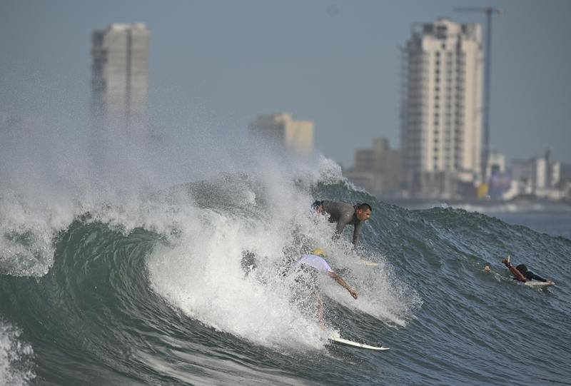 Varias personas hacen surf en la playa de Pinitos antes de la llegada de la tormenta tropical Pamela, en Mazatlán, México, el 12 de octubre de 2021. (AP Foto/Roberto Echeagaray)