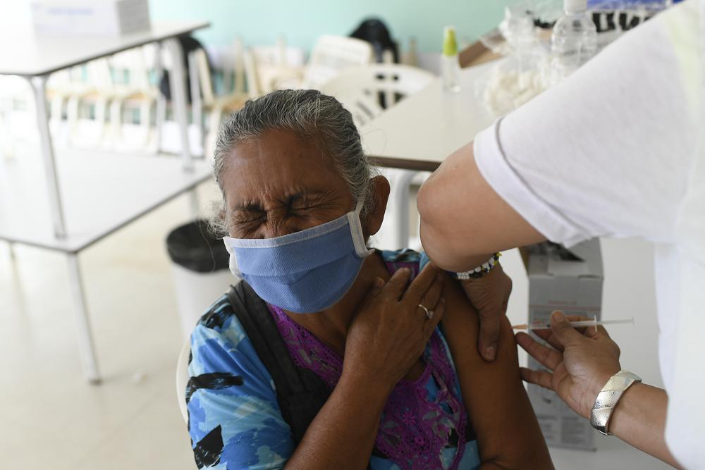 Una mujer cierra los ojos mientras recibe una inyección de la vacuna cubana Abdala contra COVID-19 en el barrio Ciudad Tiuna de Caracas, Venezuela, el martes 29 de junio de 2021. (AP Foto/Matias Delacroix)