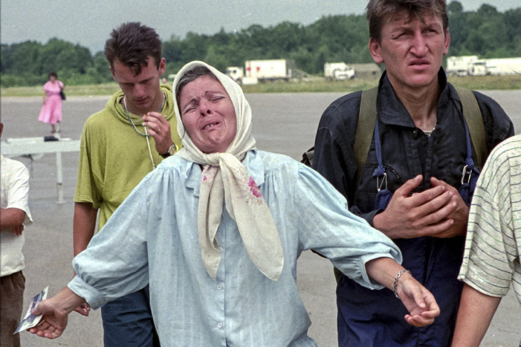 FILE- In this July 17, 1995, file picture, a Bosnian woman reacts after learning from Muslim men who arrived in Tuzla that her husband has been killed by Bosnian Serbs who overran the UN declared safe haven of Srebrenica.  Survivors of the genocide in the eastern Bosnian town of Srebrenica, mainly women, will on Saturday July 11, 2020, commemorate the 25th anniversary of the slaughter of their fathers and brothers, husbands and sons.  At least 8,000 mostly Muslim men and boys were chased through woods in and around Srebrenica by Serb troops in what is considered the worst carnage of civilians in Europe since World War II. The slaughter was also the only atrocity of the brutal war that has been confirmed an act of genocide.(AP Photo/Michel Euler, File)