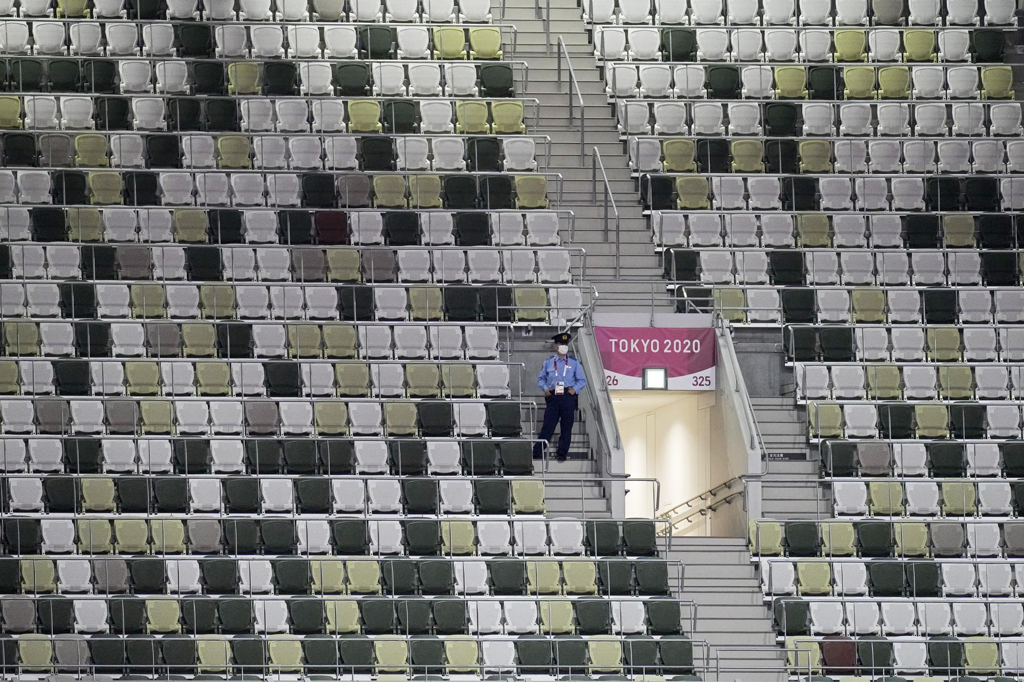 A security officer looks out over an empty stadium before the opening ceremony in the Olympic Stadium at the 2020 Summer Olympics, Friday, July 23, 2021, in Tokyo, Japan. (AP Photo/David J. Phillip)