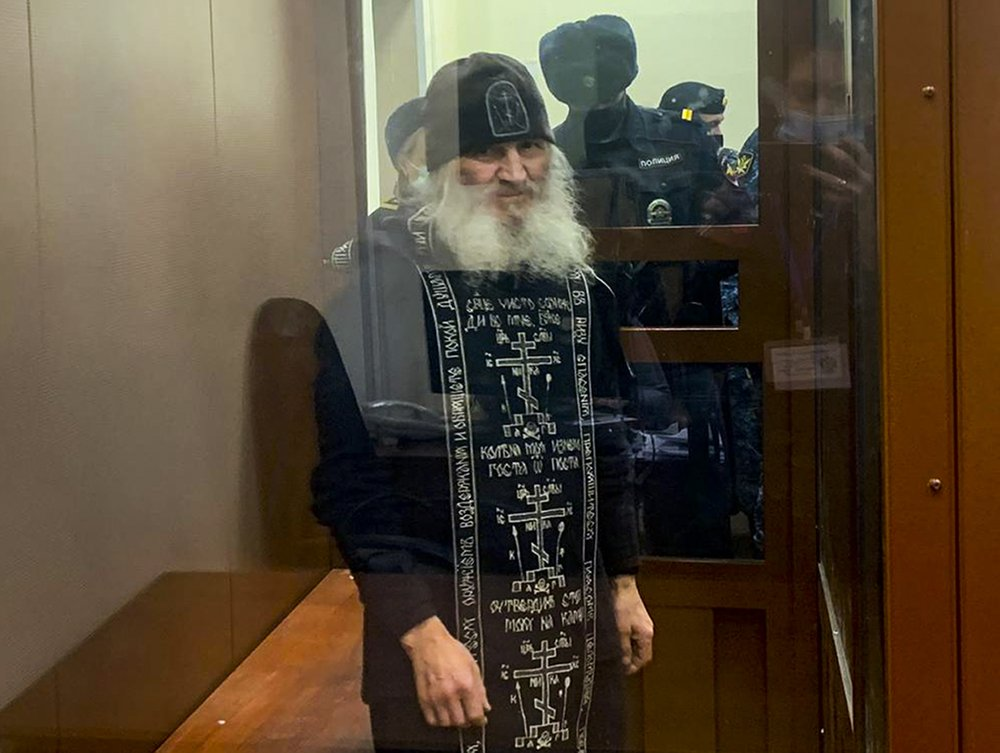 In this handout photo released by Basmanny Court via Moscow News Agency, Father Sergiy, a Russian monk who has defied the Russian Orthodox Church's leadership, stands in a cage prior to a court session in Moscow, Russia, Tuesday, Dec. 29, 2020. Father Sergiy, who has castigated the Kremlin and the Russian Orthodox Church leadership and denied the coronavirus existence, was detained Tuesday Dec. 29, 2020, by police at a monastery in the Urals and flown to Moscow where he will face criminal charges. (Basmanny Court, Moscow News Agency photo via AP)