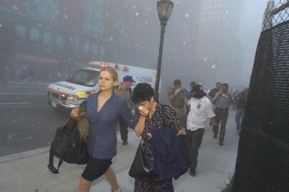FILE - People flee from downtown Manhattan after planes crashed into the twin towers of the World Trade Center on September 11, 2001 in New York City.  Associated Press photographer Richard Drew talks about AP's coverage of 9/11 and the events that followed.  (AP Photo/Richard Drew)