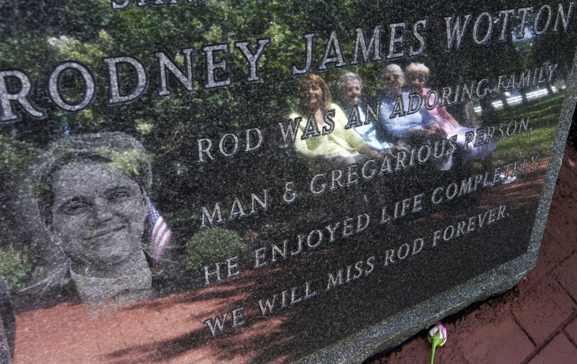 ADVANCE FOR PUBLICATION ON SUNDAY, SEPT. 5, AND THEREAFTER - FILE - In this Tuesday, Sept. 11, 2012 file photo, Pat Wotton, left, is reflected in a memorial to her husband Rodney James Wotton, as she sits with Dorothy Greene, second left, Jean Wotton, Rodney's mother, and Eunice Saporito, right, in Middletown, N.J. The marker for Rodney Wotton is one of 37 in the Middletown World Trade Center Memorial Gardens for those from the town in central New Jersey, who died in the attack on the World Trade Center in 2001AP Photo/Mel Evans, File)