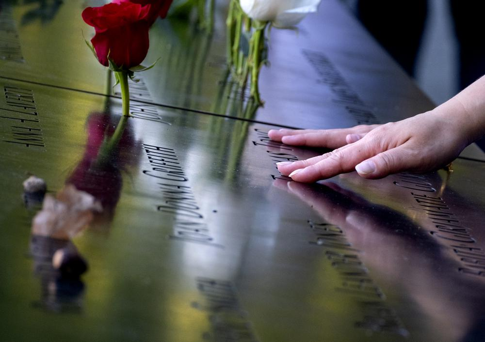 Hands touch the names of people who were killed during the attacks on the World Trade Center on Sept. 11, 2001, as families gather at the National September 11 Memorial in New York on the 20th anniversary of the attacks, Saturday, Sept. 11, 2021. (Craig Ruttle/Newsday via AP, Pool)