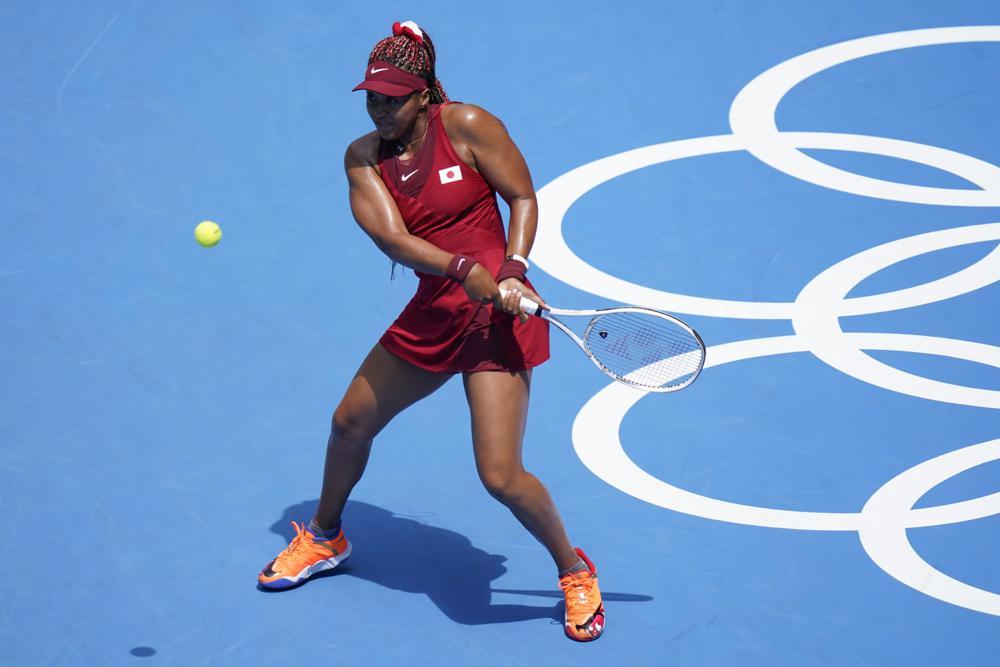 Naomi Osaka, of Japan, returns to China's Zheng Saisai during the tennis competition at the 2020 Summer Olympics, Sunday, July 25, 2021, in Tokyo, Japan. (AP Photo/Patrick Semansky)