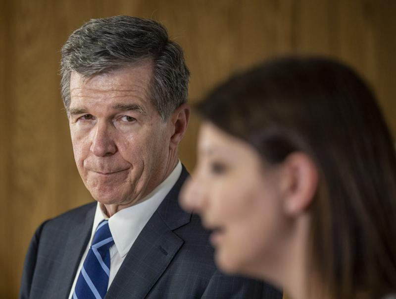 North Carolina Governor Roy Cooper looks on as Dr. Mandy Cohen speaks to the media after their tour of a COVID-19 vaccine clinic at the Pine Hall Brick plant in Madison, N.C., on Thursday, May 27, 2021. (Woody Marshall/News & Record via AP)