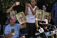 Supporters of Gabby Petito hold up photos of Gabby after a news conference Wednesday, Oct. 20, 2021, in North Port, Fla. Items believed to belong to Brian Laundrie and potential human remains were found in a Florida wilderness park during a search for clues in the slaying of Gabby Petito . (AP Photo/Chris O'Meara)