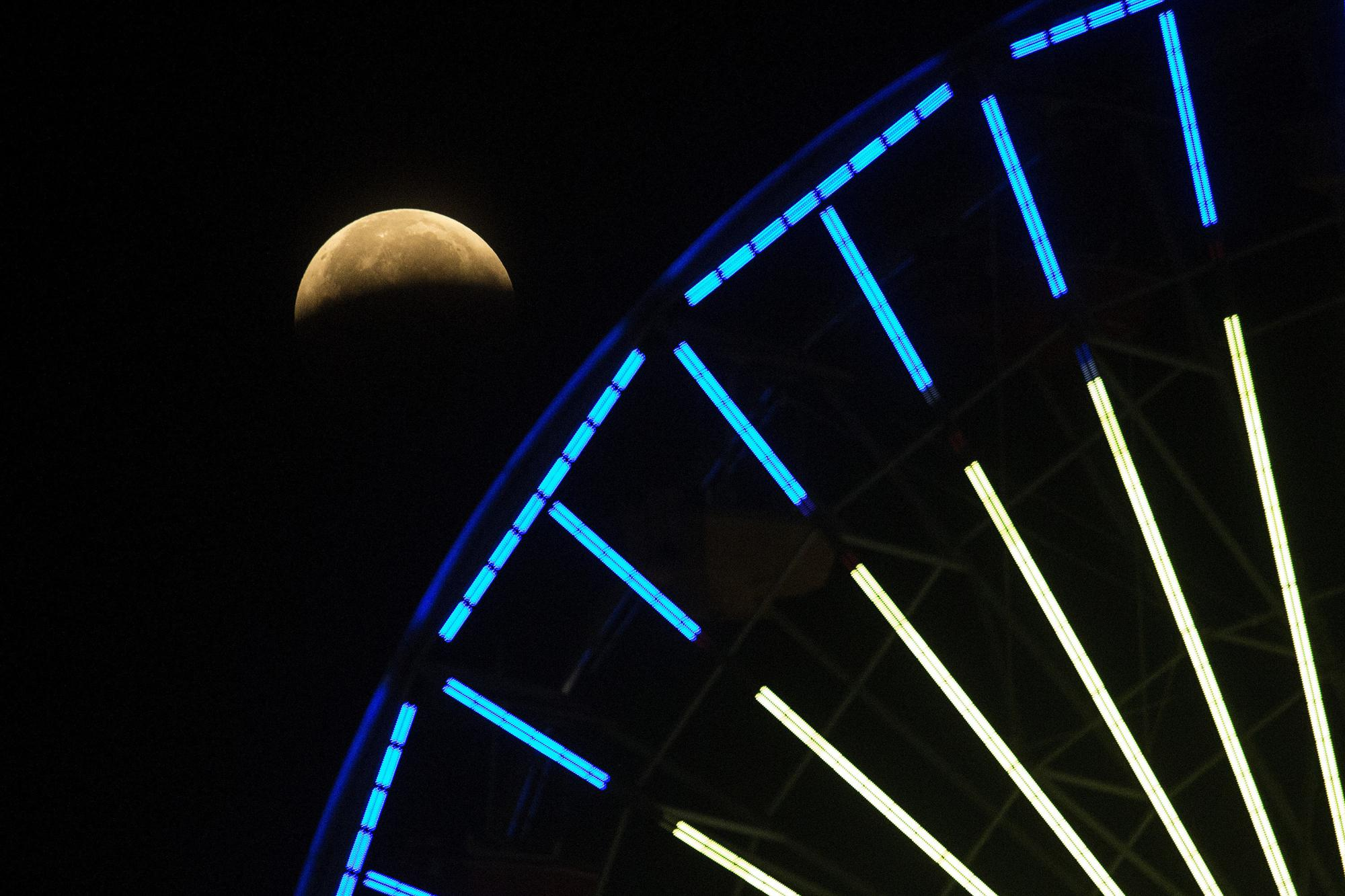 The lunar eclipse shines behind a Ferris wheel in Santa Monica, Calif., Wednesday, May 26, 2021. The first total lunar eclipse in more than two years is coinciding with a supermoon for quite a cosmic show. (AP Photo/Ringo H.W. Chiu)