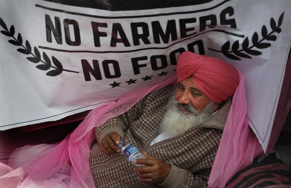In this Monday, Dec. 14, 2020, file photo, a protesting farmer rests on his tractor trailer blocking a highway with other farmers at the Delhi- Haryana border, on the outskirts of New Delhi, India. Relations between Twitter and Modi's government have gone downhill ever since a tweet by pop star Rihanna in February sparked widespread condemnation of Indian Prime Minister Narendra Modi's handling of massive farmer protests near the capital. At the heart of the standoff is a sweeping internet law that puts digital platforms like Twitter and Facebook under direct government oversight. Critics of the law worry it may lead to outright censorship in a country where digital freedoms have been shrinking since Modi took office in 2014.