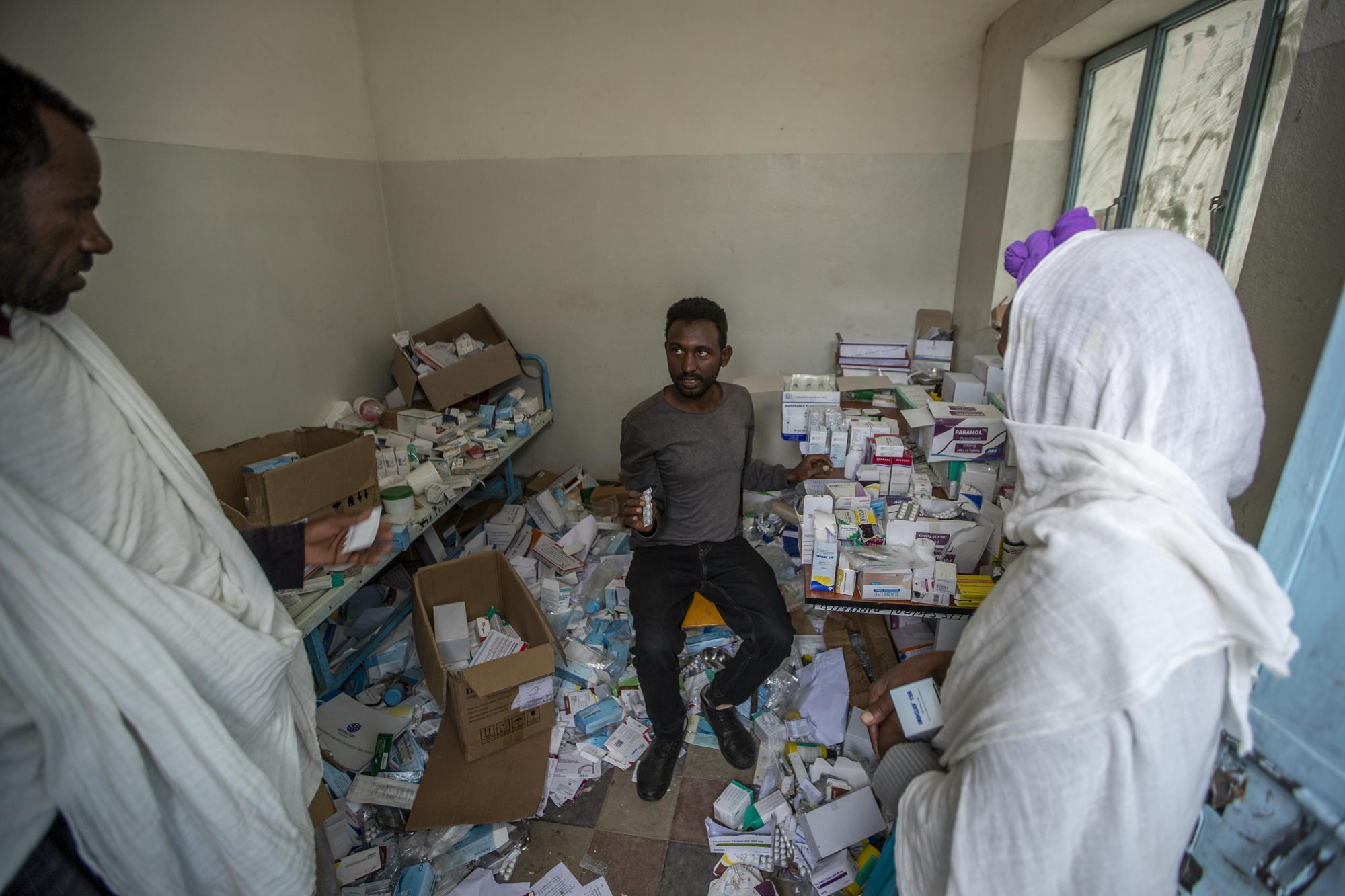 A pharmacist, center, speaks to patients as he sits among the packages of medicine able to be recovered in Hawzen, in the Tigray region of northern Ethiopia, on Friday, May 7, 2021. The hospital was damaged and looted by Eritrean soldiers who used it as a base, according to witnesses. (AP Photo/Ben Curtis)