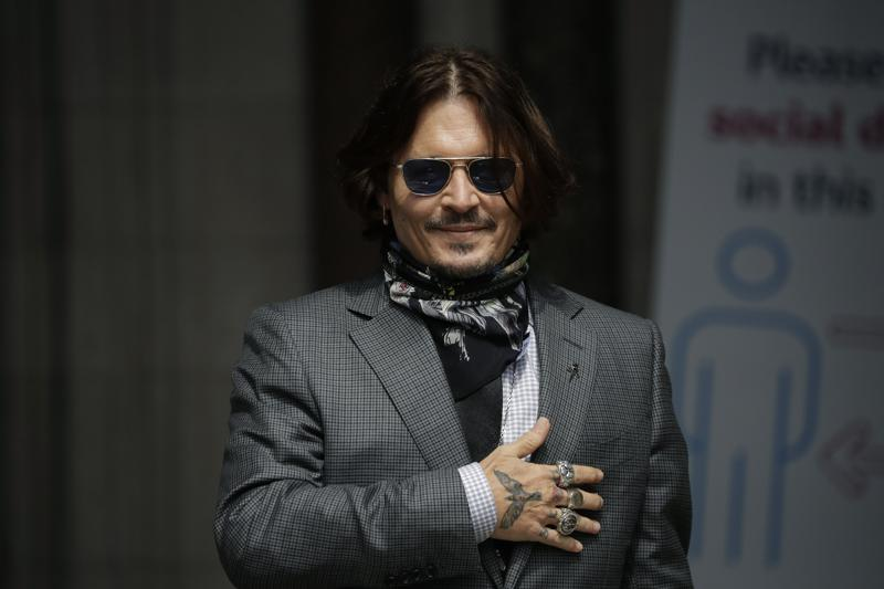"""FILE - In this Thursday, July 23, 2020 file photo, U.S. actor Johnny Depp gestures to fans and the media as he arrives at the High Court in London. Spain's most high-profile group of female filmmakers denounced the San Sebastian film festival's decision to award Johnny Depp its highest honor for acting on Monday Aug. 9, 2021. The move gives the festival a bad name after a British judge ruled allegations of domestic violence against Depp were """"substantially correct"""", it says. (AP Photo/Matt Dunham, file)"""