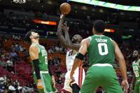 Miami Heat center Dewayne Dedmon (21) shoots over Boston Celtics center Enes Kanter (13) and forward Jayson Tatum (0) during the first half of a preseason NBA basketball game, Friday, Oct. 15, 2021, in Miami. (AP Photo/Lynne Sladky)